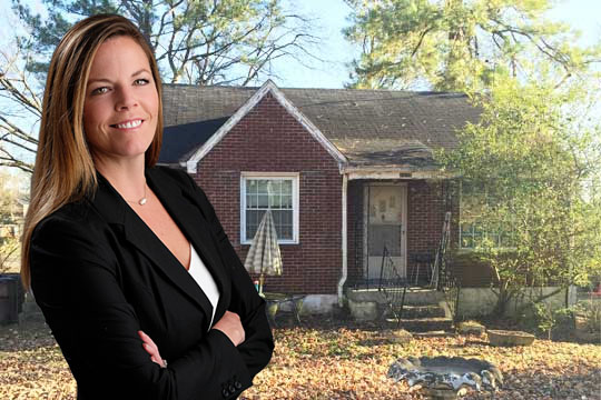 Picture of Stacy Desoto standing in front of one of the ugly houses she bought for cash in Nashville, TN
